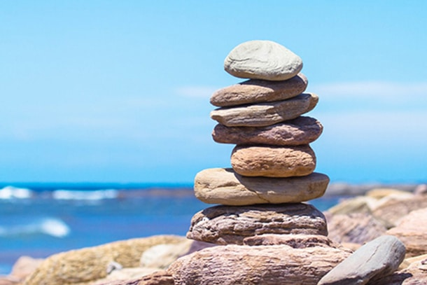 stacked balancing rocks practicing patience and serenity for mental health improvement